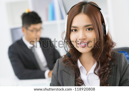 Pretty customer support representative with a pleasant smile working from office - stock photo