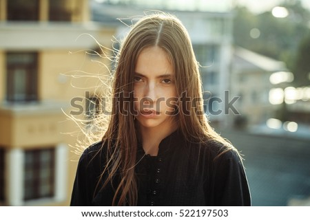 Pretty cute sexy girl young beautiful woman with long brunette hair in black shirt outdoors near houses and buildings on blurred or defocused background