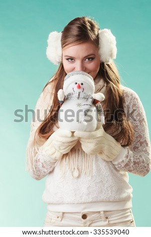 Pretty cute woman holding little snowman. Attractive girl in earmuffs and white sweater pullover in studio on green. Winter fashion.