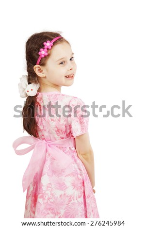 Pretty cute young girl wearing the pink dress looking back - stock photo