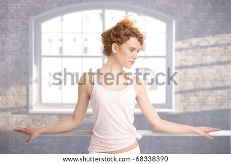 Pretty dancer standing by bar in dance studio front of window. - stock photo
