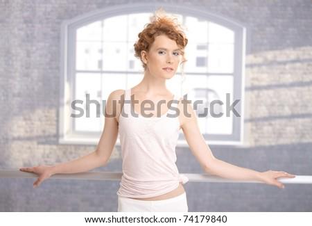 Pretty dancer standing by bar in dance studio front of window.? - stock photo
