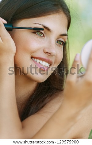 Pretty dark-haired funny young woman dyes her eyelashes, against background of summer green park. - stock photo