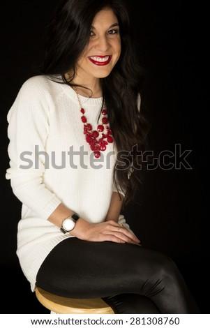 Pretty dark model sitting on barstool smiling - stock photo