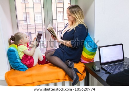 Pretty daughter with young mother read books on window sill - stock photo
