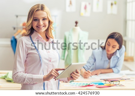Pretty designer with tablet is looking at camera and smiling, working in dressmaking studio, in the background another designer is drawing sketches
