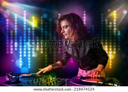 Pretty Dj girl playing songs in a disco with light show - stock photo