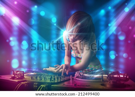 Pretty Dj mixing music in a club with blue and purple lights - stock photo