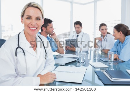 Pretty doctor smiling to the camera while her team works - stock photo