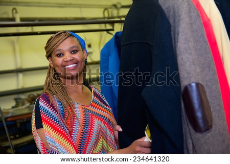 Pretty dry cleaner woman does her job in laundry - stock photo