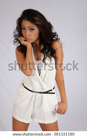 Pretty East Asian woman in white outfit,  looking seriously at the camera