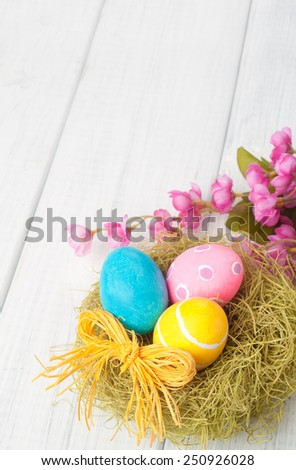 Pretty Easter Eggs in Nest with Pink Flowers in lower framework on Rustic White Wash Painted Board Background with empty, blank room or space for copy, text, your words.  Vertical above view - stock photo