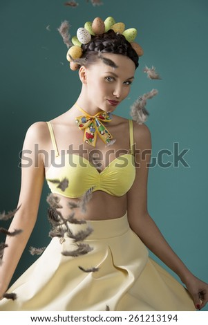 Pretty easter woman in yellow dress and bra. she has got brown, funny hairstyle with eggs. There is flying feathers everywhere. - stock photo