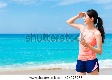 pretty elegant fitness woman standing on beach using mobile cell phone searching local information and looking for travel landscape.
