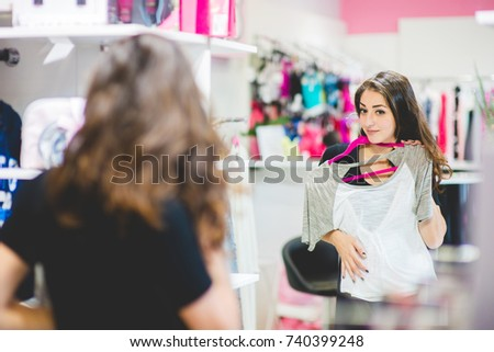 Pretty elegant woman looking at the mirror in clothes store