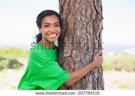 Pretty environmental activist hugging tree on a sunny day in the countryside - stock photo