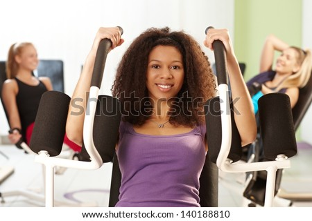 Pretty ethnic girl doing arm exercises at the gym on exercise machine, smiling. - stock photo