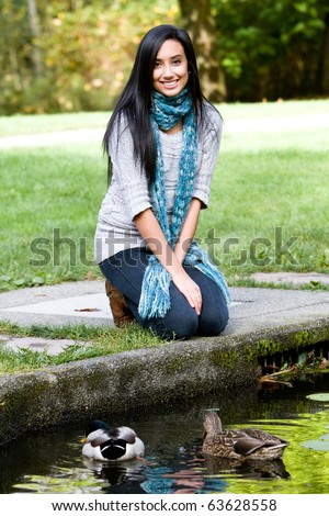 Pretty ethnic girl feeding ducks