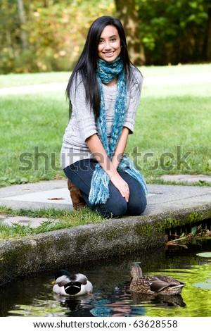 Pretty ethnic girl feeding ducks - stock photo