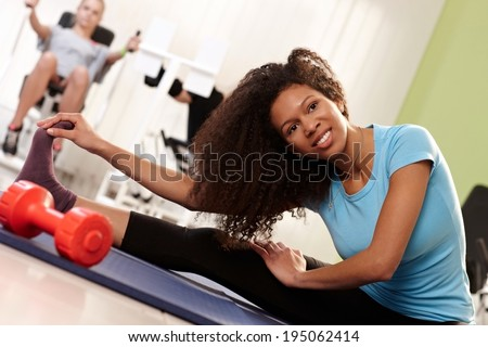 Pretty ethnic woman doing stretching exercises at the gym, touching toe. - stock photo