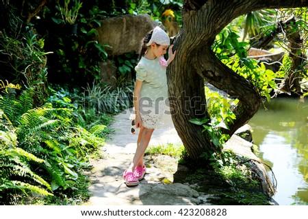 Pretty european brunette girl near th huge tree in tropical garden - stock photo