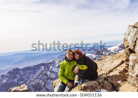 Pretty, european, couple sitting in the mountains. top of Toubkal, High Atlas, Morocco, Africa.