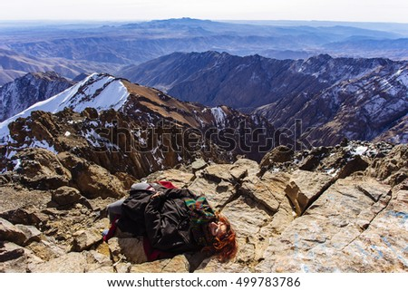 Pretty, european red haired girl resting, lying on the ground, on the top of Tubkal, with Atlas mountains in the background. Morocco.
