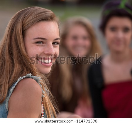 Pretty European teenage girl with smile looking over shoulder - stock photo