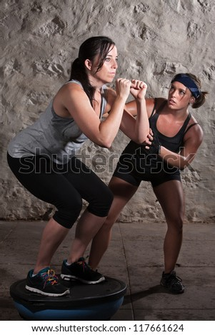 Pretty European woman on balancing equipment for boot camp workout - stock photo