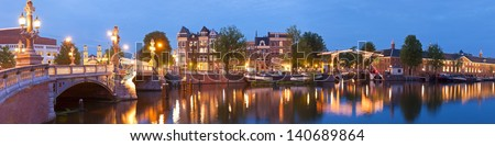 Pretty evening illuminations of the historic and richly decorated Blauwbrug (1883) bridge in Amsterdam. Skinny bridge and Stopera music theatre visible. Stitched panoramic image. - stock photo