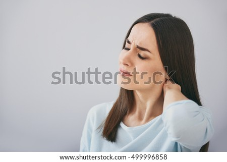 Pretty exhausted woman closing eyes and standing against white wall.