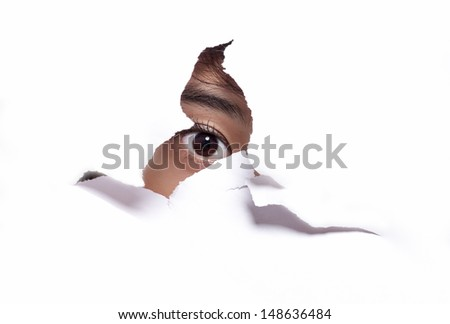 Pretty eye looking through a hole in a paper. - stock photo