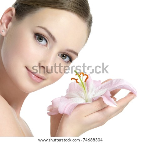 Pretty face of beautiful young woman with lily on hands - white background