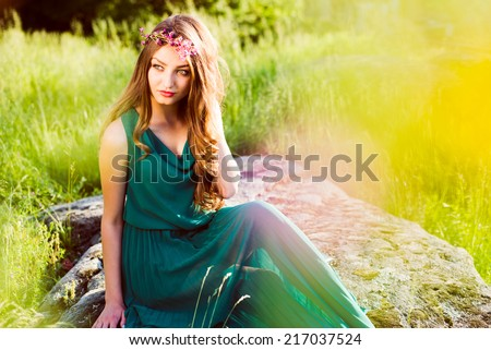 pretty fairy: young woman cute brunette girl sitting on stone in green dress with pink wreath of flowers & sun light flares of rays & looking at camera on summer outdoor copy space background - stock photo