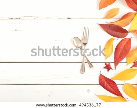 Pretty Fall Table Setting with Colorful Leaves and a fork and spoon from above on Rustic Painted White Board Background.  It's Simple and Casual with blank room or space for copy, text, your words.