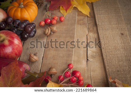 Pretty Fall Vignette with Mini Pumpkin, Apple, Red Pear, Nuts, Grapes, leaves and berries on rustic barn wood boards with room or space for copy, text, words.  Horizontal, above view at angle - stock photo