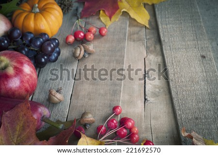 Pretty Fall Vignette with Mini Pumpkin, Grapes, Apple, Pear, Nuts, Leaves on Rustic Used Board Background with empty space for copy, text, words.  Horizontal above view, cool toned. - stock photo