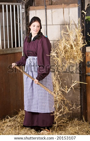 Pretty farmergirl working in the stable throwing new straw in the box - stock photo