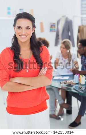 Pretty fashion designer with arms crossed in bright office smiling at camera - stock photo