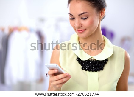 Pretty fashion designer working in office using mobile phone. - stock photo