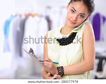 Pretty fashion designer working in office using mobile phone . - stock photo