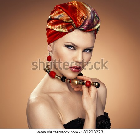 Pretty fashion girl in turban wearing red earrings, touching her necklace. Beautiful Caucasian blue eyed model with ethnic make-up and hairstyle.