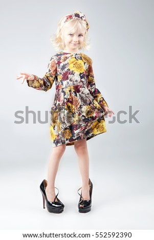 Pretty fashion little girl trying on mothers shoes on high heels. Fashion children concept. White background.