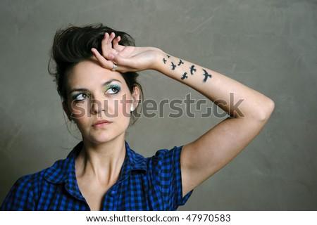 Pretty fashion model with wild hair poses in studio - stock photo