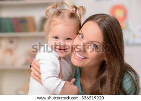 Pretty father are her daughter are embracing. They are smiling and looking at the camera happily - stock photo