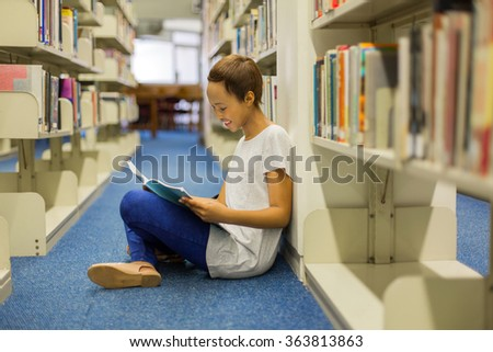 pretty female african american student sitting on the floor reading a book in library