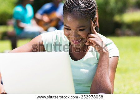 pretty female african college student working on laptop computer - stock photo