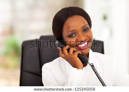 pretty female african office worker talking on phone - stock photo