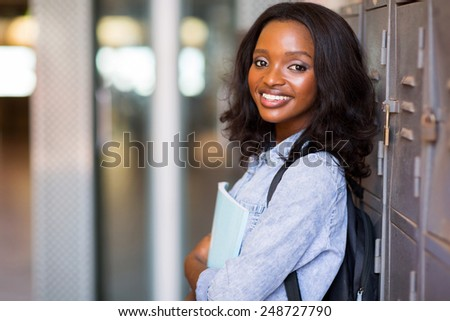 pretty female african student standing next to locker at college - stock photo