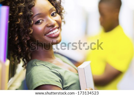pretty female african uni student holding a book in library